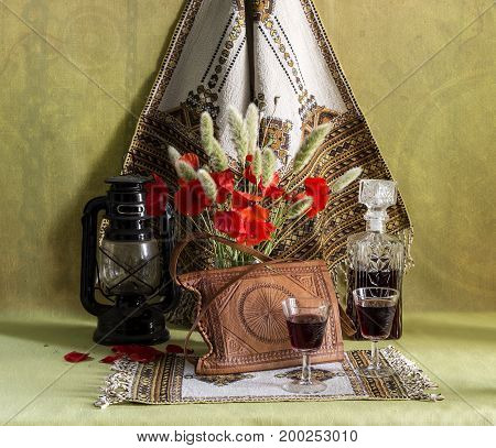 Bottle and two glasses with brandy and a bouquet of red poppies on the table closeup