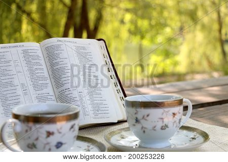 wooden table open book a number of cups of coffee