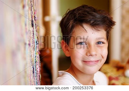 Boy sitting in the kitchen waiting for dinner with a smile