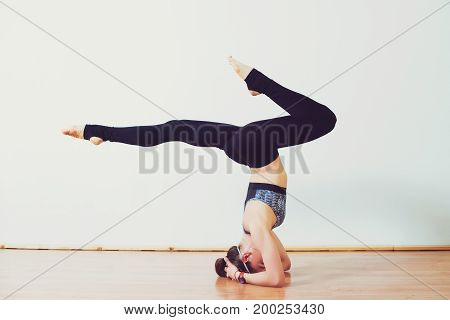 Young attractive woman practicing yoga in the studio. Girl standing in headstand exercise salamba sirsasana pose working out wearing sportswear indoor full length.