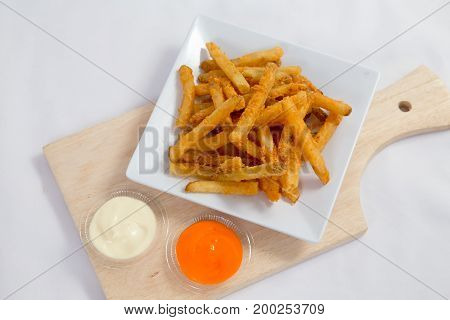 Hot and spicy french fries on a white plate with mayonnaise and cheese sauce