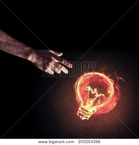 Close of man hand showing at glowing fire light bulb icon