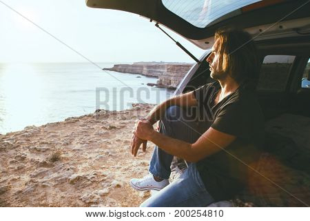 Man relaxing inside car trunk and watching on sea. Fall trip in sunset. Freedom travel concept. Autumn weekend.