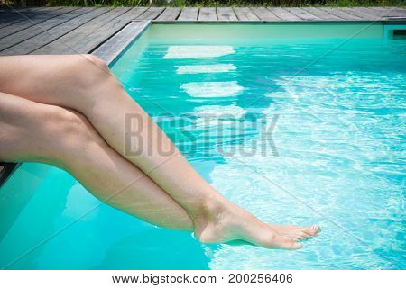 Beautiful Pair Of Legs Of Women In Summer In The Blue Swimming Pool Of Holidays And Relaxation