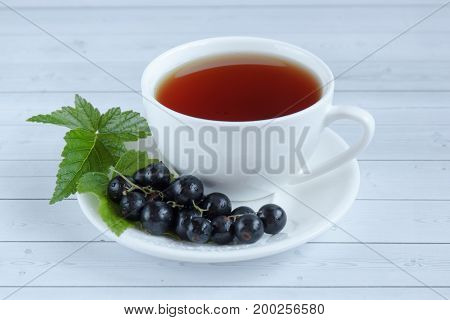 Cup of tea and black currant on a wooden background