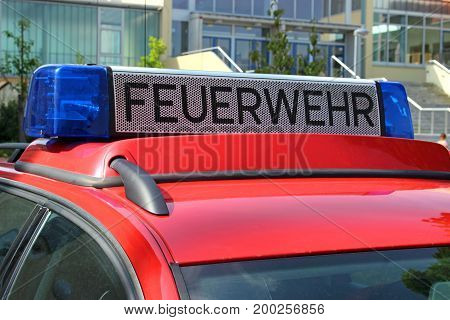 german red fire brigade car with blue light in front od a school close-up