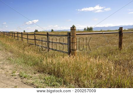 wood and wire fence by a prairie in Colorado. The Rockie Mountains are in the background