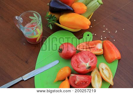 Tomatoes and peppers sliced on cutting board and glass of tomato juice оn wooden table. Nearby there is dish with zucchini and sweet pepper. Close up.