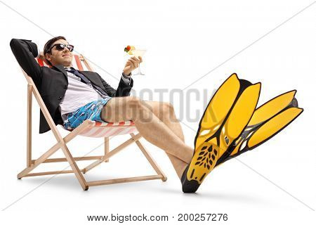 Businessman with swimming fins and a cocktail lying in a deck chair isolated on white background