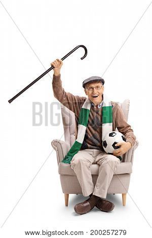 Joyful elderly soccer fan with a scarf and a football sitting in an armchair isolated on white background