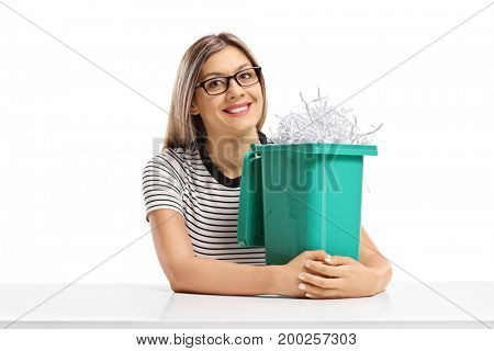 Young woman with a garbage bin filled with shredded paper sitting at a table isolated on white background