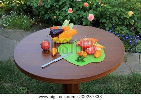 Tomatoes and peppers sliced on cutting board оn wooden table in garden patio with flowers. Nearby there is dish with zucchini and sweet pepper.
