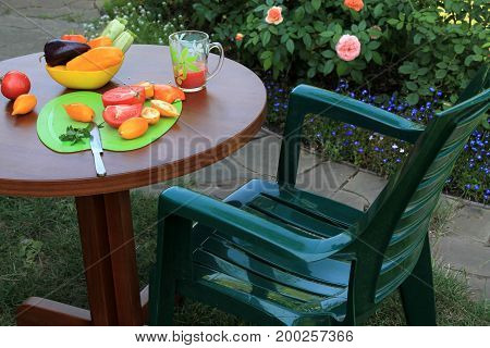 Armchair and wooden table with sliced tomatoes and peppers and glass of juice in garden patio with flowers. Nearby there is dish with zucchini and sweet pepper.