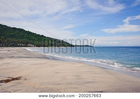 Fabulous view on a tropical island is a deserted beach with white sand, palm trees, mountains and an ocean of turquoise color under a blue sky. Journey to a tropical island in the ocean.