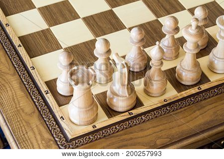 Beautiful wooden chess figures on a wooden luxury chessboard at the lounge area.