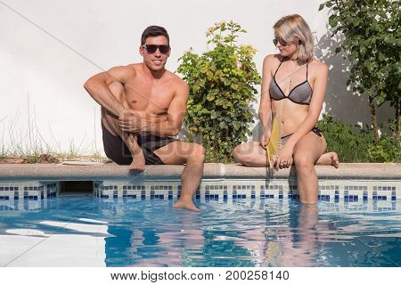 Young muscular man sitting on poolside with girl and talking in sunlight.