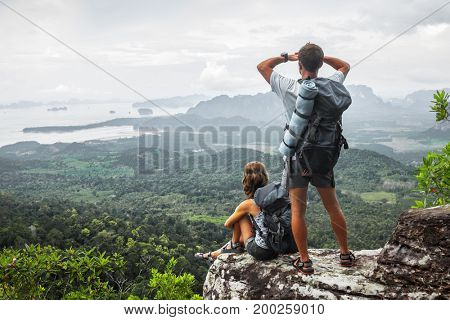 Two hikers relax on top of a mountain with great view