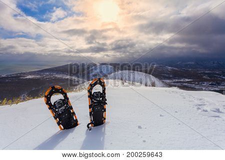 Professional snowshoes in the snow on the winter mountains and sky with clouds background. Snowshoeing.