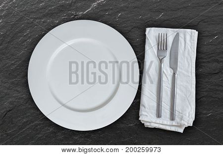 Empty plate with cutlery on slate background.