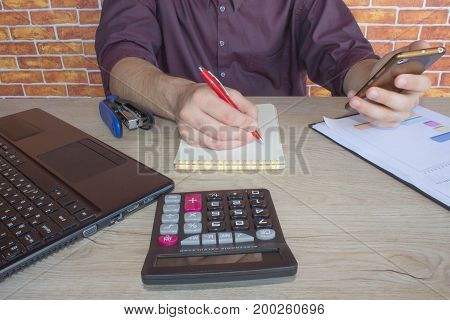 Close up of businessman hand holding pen working on calculator accountancy document and laptop computer at office e business concept. Businessperson working in office