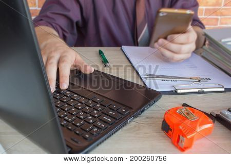 Man hand with calculator at workplace office. Young man paying bills with his laptop