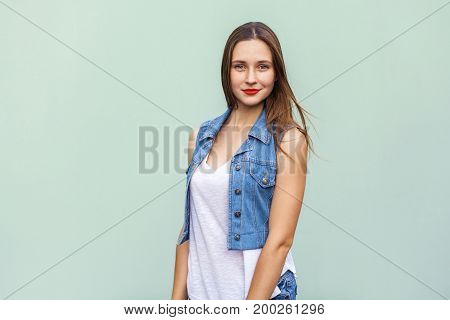 The tender and cute teenage female with shy faint smile freckles and and clean skin looking at camera and posing indoors against light green studio wall.