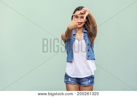 Creative young adult woman with freckles making a frame gesture with her fingers as she looks through to visualise a project or the composition of a photograph. Indoor studio shot on light green background