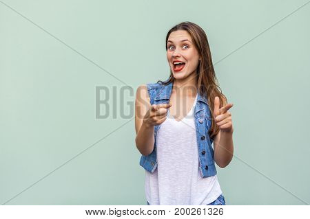 Happy cheerful teenage girl with freckles casual style white t shirt and jeans jacket looking at camera pointing two fingers at camera having joyful look enjoying good day and free time indoors. Studio shot