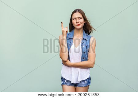 Pretty casual style girl with freckles got the idea and she raised her finger up and thinking. Isolated studio shot on light green background