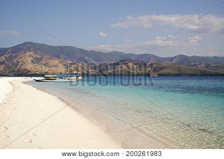 White Sand Beach With Two Boats On Shore At Midday Overlooking Broad Island With Green Vegetation In
