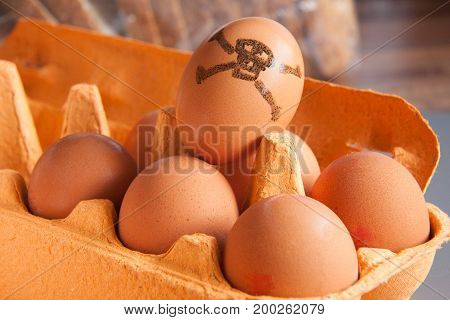 Tray of brown eggs,one marked with a hand drawn skull & crossbones.
