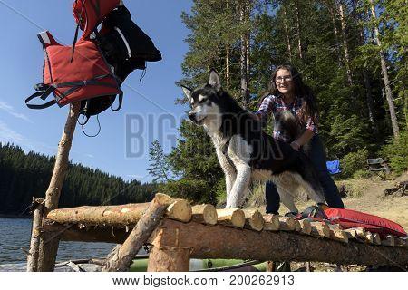 Teenager girl holding Alaskan Malamute on a pier