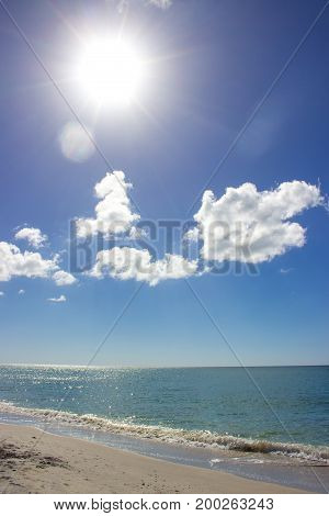 A beach with brilliant blue skies at mid-day