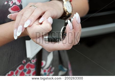 Female with manicured nails holding brand new car keys closeup photo