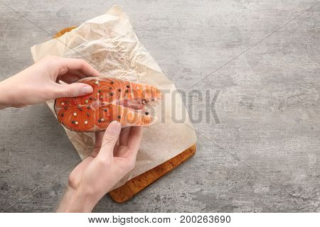 Woman holding fresh salmon steak with peppers mix over table