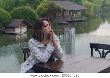 Woman at a cafe table by the pond. People