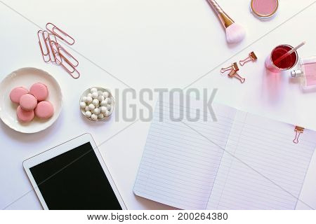 Modern styled desk top with rose gold accents, beauty products, sweets, drink, tablet and note book. White copy space.