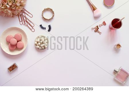Modern styled desk top with rose gold accents, fashion and beauty items, sweets, drink and flowers. Copy space.