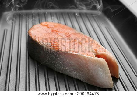 Piece of salmon in grill frying pan, closeup