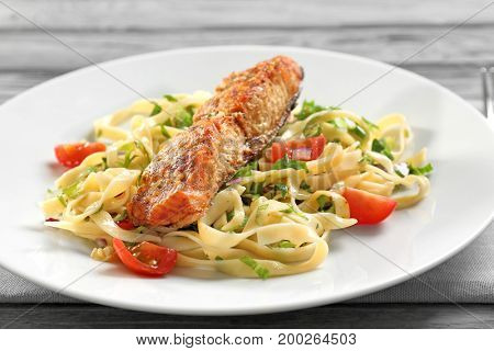 Plate with pasta, salmon and cherry tomatoes, closeup