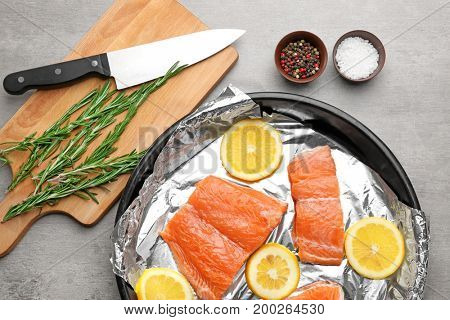 Frying pan with foil, slices of lemon and salmon on light table