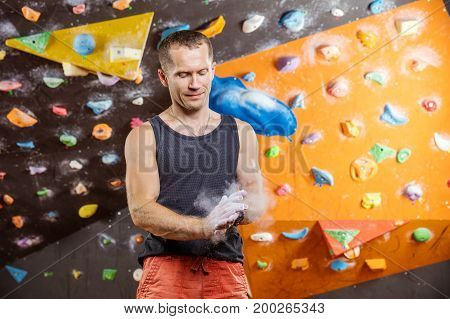 Rock climber putting chalk on hands in indoor climbing gym