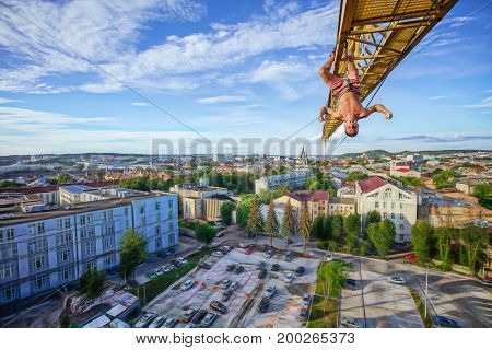 Urban climbing: rock climber hanging upside down on jib of construction crane. Panoramic view of city at background.