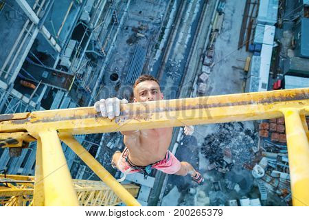 Urban climbing: rock climber hanging on jib of construction crane with one hand view of construction site below
