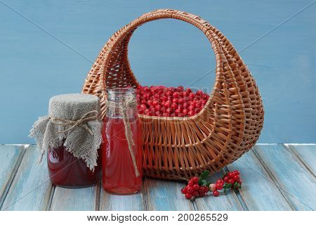 Beautiful basket full of berries cowberrys. Jam in a glass jar and drink red. Sprigs of cowberrys lying on wooden surface. Blue background.