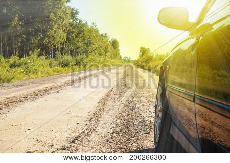 car on a rural road without asphalt