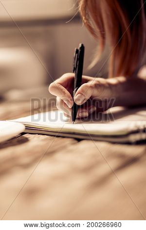 Close up view of womans hand writing in notebook. Girl making notes with pen on wooden table.