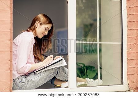 Pretty young girl sitting on windowsill. Woman making notes, holding notebook on her knees.