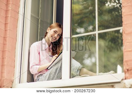 Happy smiling girl on windowsill. Female studying at home, reading synopsis of lecture.