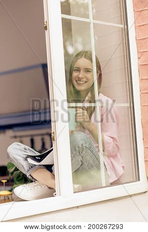 Girl sitting on windowsill holding cup in her hands. Young smiling woman drinking tea or coffee close to open window.